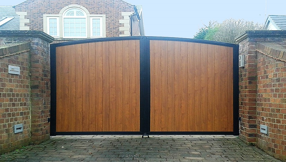 Driveway gates with curved top and aluminium panels designed to look like wood.