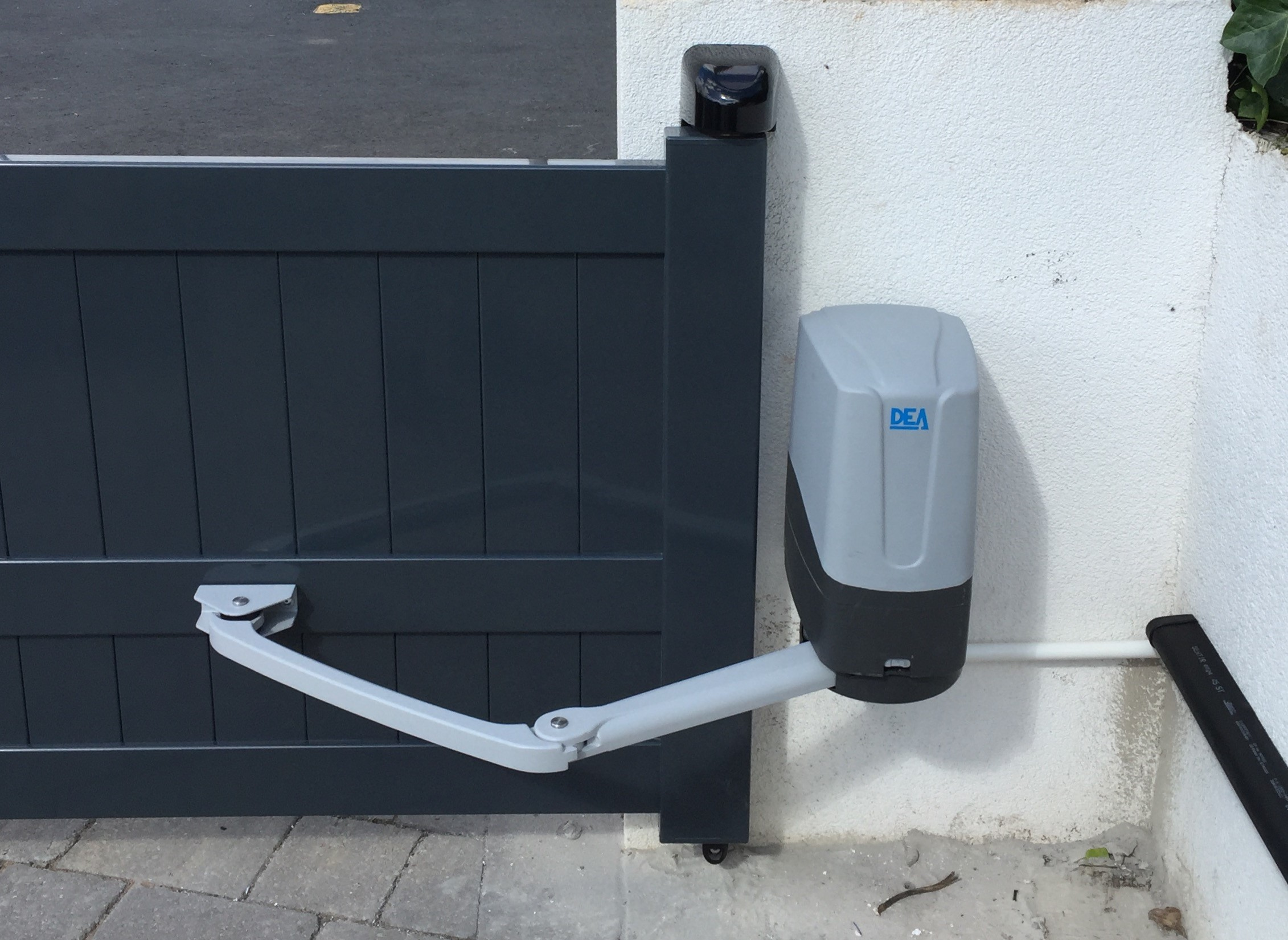 A articulated arm gate automation system on a short modern gate