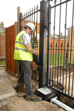 workman in high vis fixing electric gate