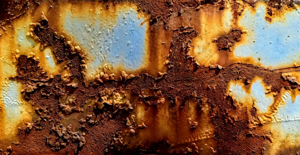 close up of brown and orange rust with peeling paint