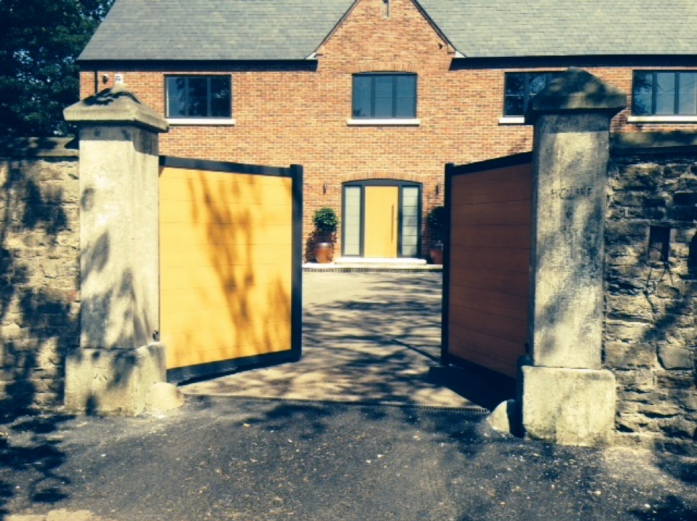 A picture of an automated open gate in front of a house