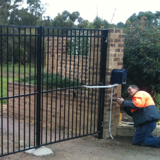 workman fixing a black automated gate
