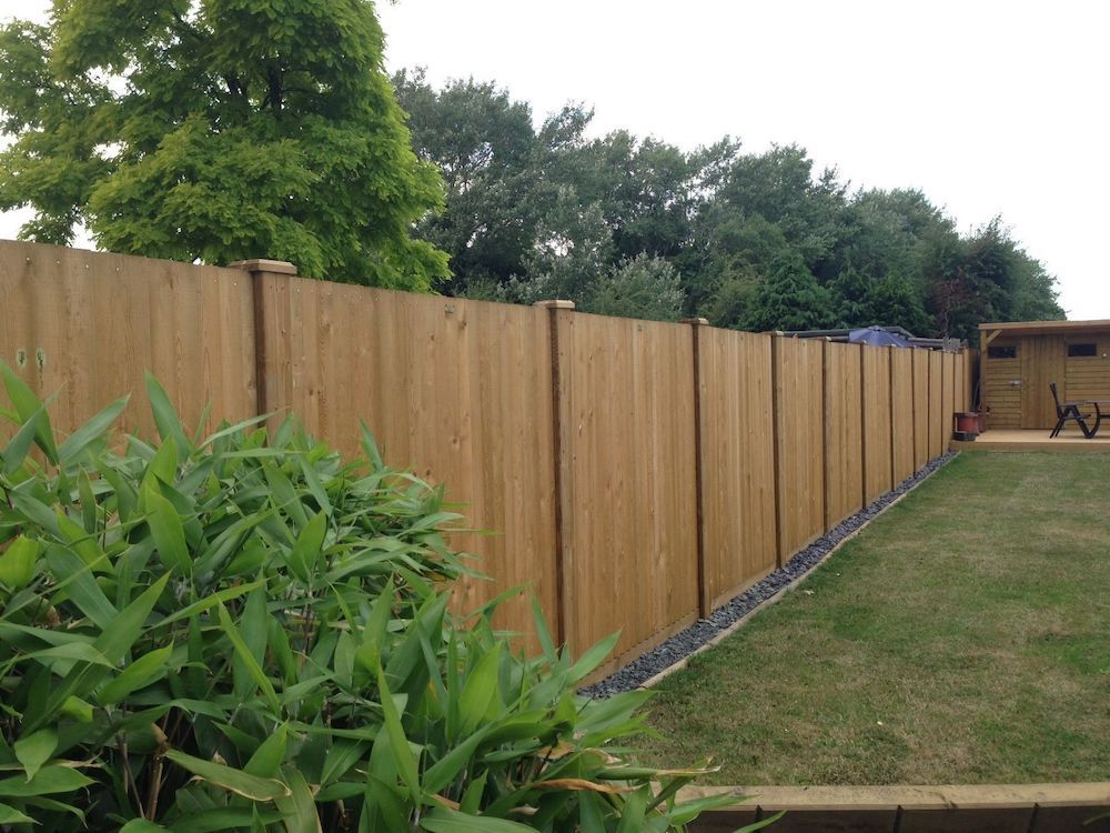 a wooden fence around the outside of a garden