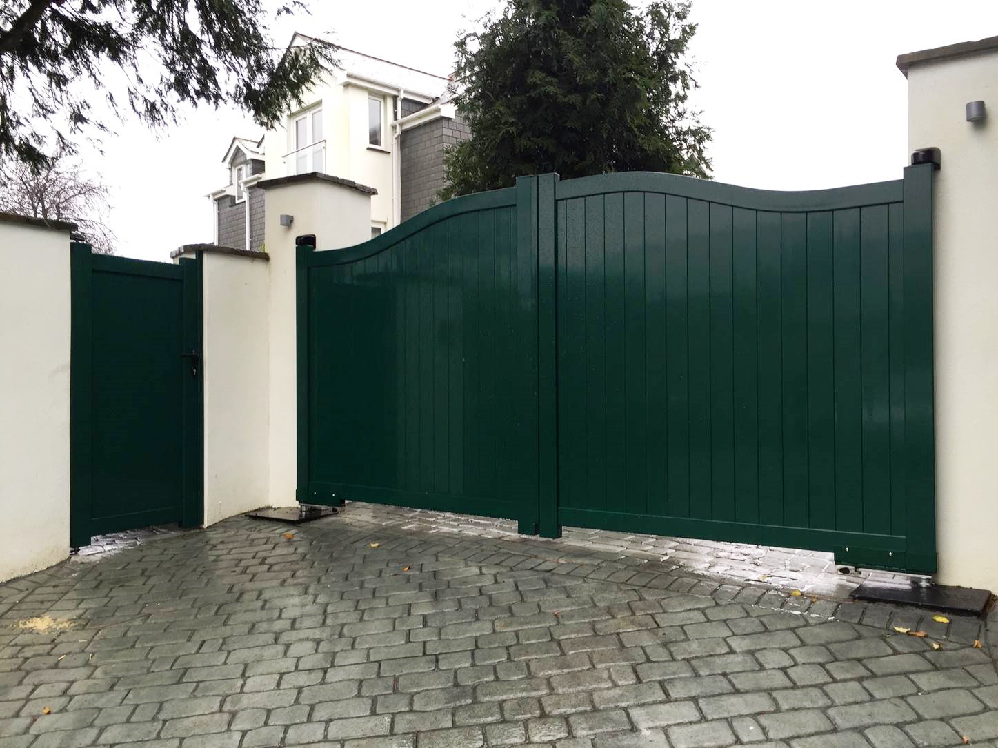 Automatic gates opening outwards on sloping drive